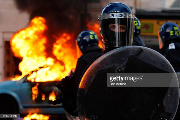 Riot police stand in front of a burning car during riots in Clarence Road Hackney on August 8 2011 in London England Pockets of rioting and looting...