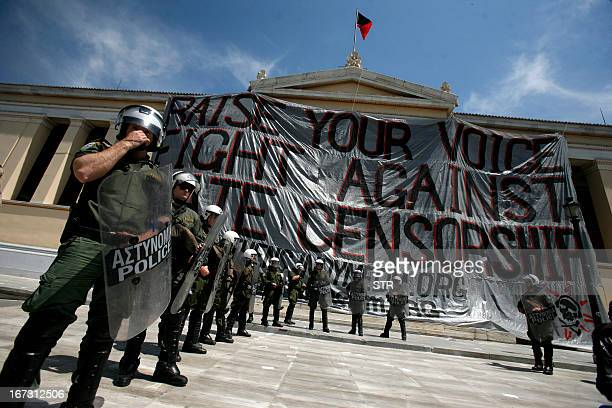 Riot police stand in front of Athens University as a renegade flag floats at the top of the of entrance Athens University above a giant banner hung...