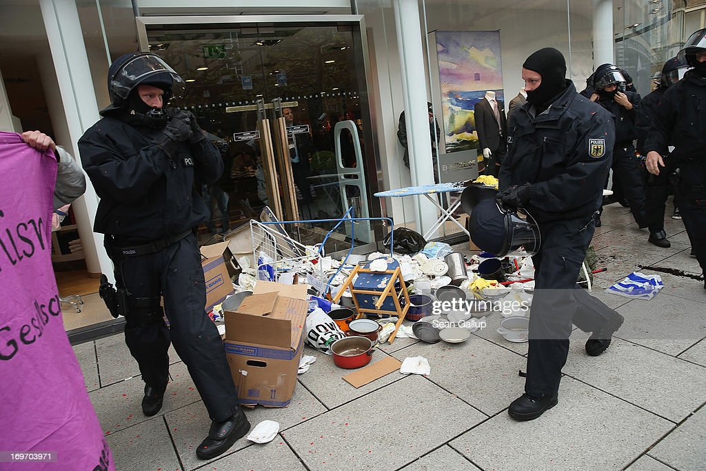 Riot police stand near garbage and other refuse dumped at the entrance to a clothing store by Blockupy protesters in the Zeil pedestrian shopping street on May 31, 2013 in Frankfurt am Main, Germany. Several thousand protesters are taking part in Blockupy protests today and tomorrow in Frankfurt in order to demonstrate aginst ECB debt policy, food prices speculation by Deutsche Bank and the labor practices inherent in the discount clothing industry.