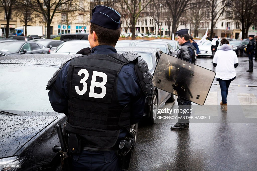 A riot police stand next to cars on the Place de la Nation in Paris on February 9, 2016, during a demonstration by non-licensed private hire cab drivers, known in France as VTC (voitures de tourisme avec chauffeur or tourism vehicles with chauffeur). VTC drivers continued a fifth day of protests on February 9 against measures granted by the French prime minister to taxi drivers. / AFP / Geoffroy Van der Hasselt