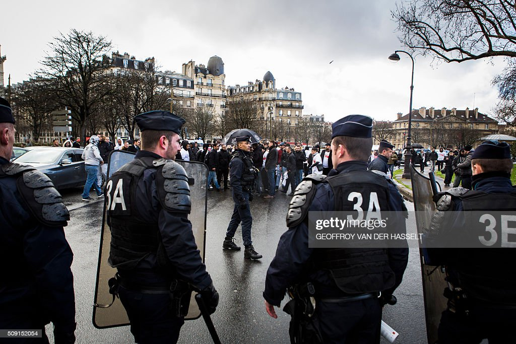 Riot police stand on the Place de la Nation in Paris on February 9, 2016, during a demonstration by non-licensed private hire cab drivers, known in France as VTC (voitures de tourisme avec chauffeur or tourism vehicles with chauffeur). VTC drivers continued a fifth day of protests on February 9 against measures granted by the French prime minister to taxi drivers. / AFP / Geoffroy Van der Hasselt