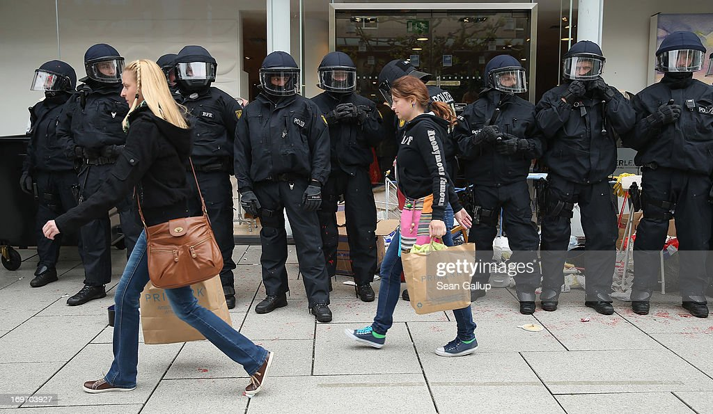 Riot police stand outside a clothing store as Friday shoppers walk past during Blockupy protests in the Zeil pedestrian shopping street on May 31, 2013 in Frankfurt am Main, Germany. Several thousand protesters are taking part in Blockupy protests today and tomorrow in Frankfurt in order to demonstrate aginst ECB debt policy, food prices speculation by Deutsche Bank and the labor practices inherent in the discount clothing industry.