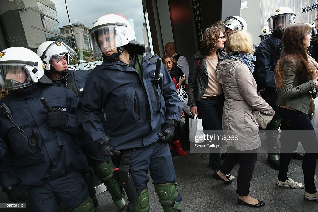 Riot police stand outside an Esprit clothing store after evicting Blockupy protesters and as shoppers stream out of the store in the Zeil pedestrian shopping street on May 31, 2013 in Frankfurt am Main, Germany. Several thousand protesters are taking part in Blockupy protests today and tomorrow in Frankfurt in order to demonstrate aginst ECB debt policy, food prices speculation by Deutsche Bank and the labor practices inherent in the discount clothing industry.