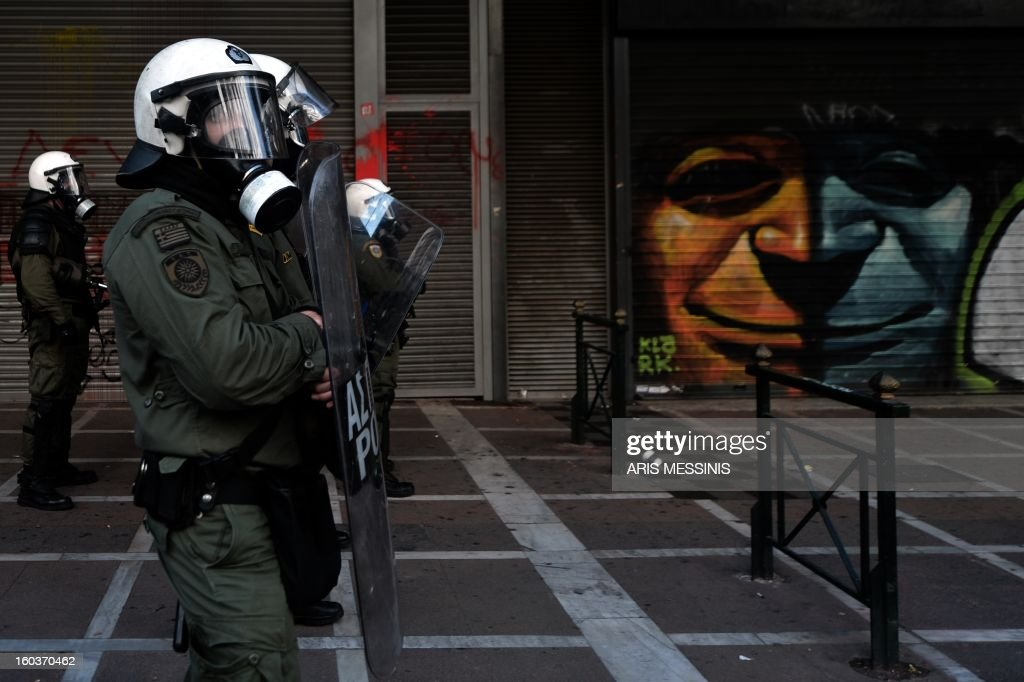 Riot police stand outside the Labour Ministry in Athens on January 30, 2013. Police were called in on Wednesday to dislodge around 30 Communist unionists from the labour ministry in a protest against new pension cut plans. The unionists were arrested and police used tear gas outside the building to disperse a larger group of protesters demanding their release.