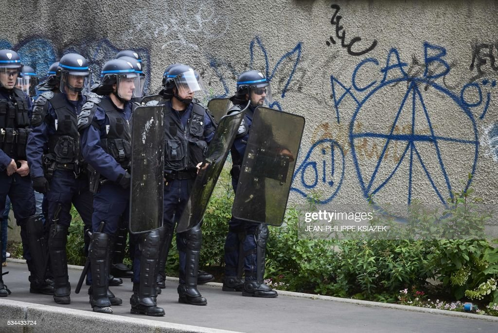 Riot police stands next to an inscription an a wall reading 'ACAB' during a demonstration against the government's planned labour reform, on May 26, 2016 in Lyon, central eastern France. The French government's labour market proposals, which are designed to make it easier for companies to hire and fire, have sparked a series of nationwide protests and strikes over the past three months. Masked youths clashed with police in Paris and striking workers blockaded refineries and nuclear power stations on May 26, 2016 as an escalating wave of industrial action against labour reforms rocked France. KSIAZEK