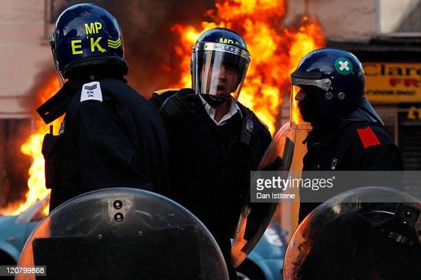 Riot police talk in front of a burning car during riots in Clarence Road Hackney on August 8 2011 in London England Pockets of rioting and looting...