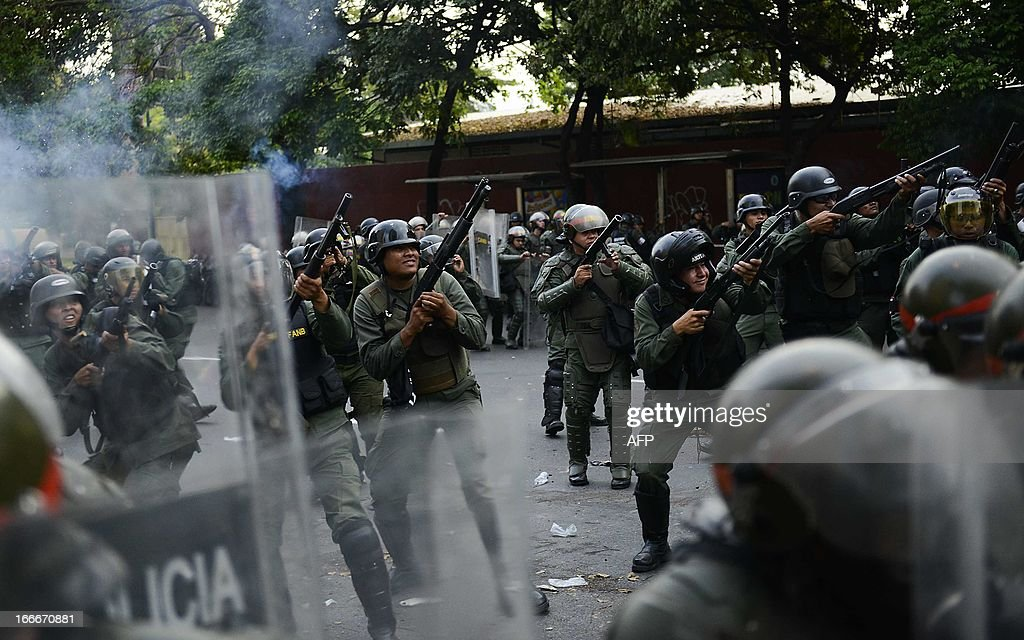Riot police throw tear gas to supporters of Venezuelan opposition presidential candidate Henrique Capriles as they protest in Caracas on April 15, 2013. Venezuela's acting President Nicolas Maduro was proclaimed the winner of an election to succeed late leader Hugo Chavez here Monday triggering protests as the opposition demanded a recount. AFP PHOTO/Leo Ramirez