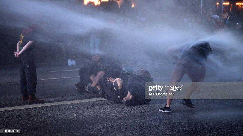 TOPSHOT - Riot police use a water cannon against protesters after the 'Welcome to Hell' rally against the G20 summit in Hamburg, northern Germany on July 6, 2017. Leaders of the world's top economies will gather from July 7 to 8, 2017 in Germany for likely the stormiest G20 summit in years, with disagreements ranging from wars to climate change and global trade. / AFP PHOTO / Christof STACHE
