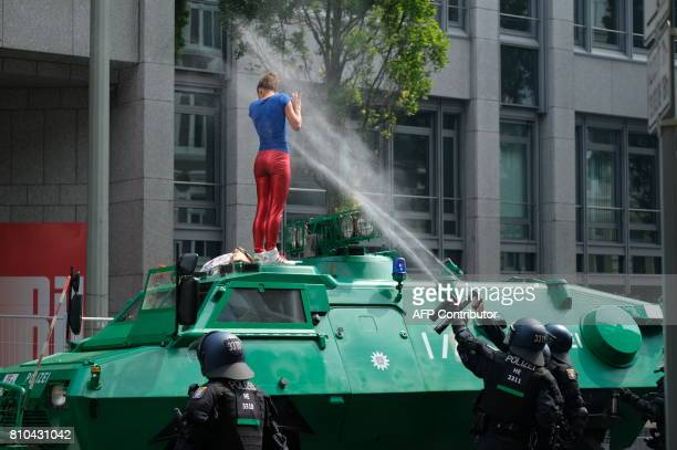 Riot police use pepper spray on a protester who climbed on top of a Police armoured vehicle on July 7 2017 in Hamburg northern Germany where leaders...