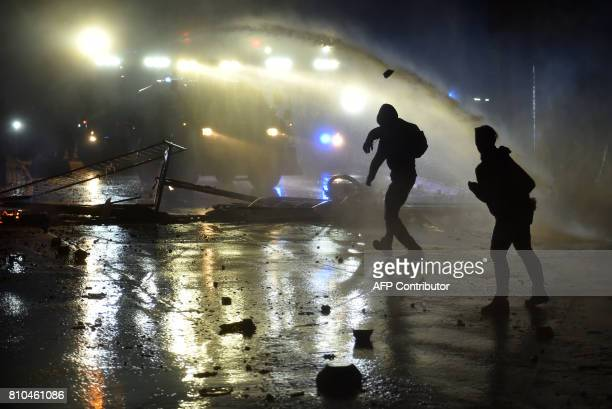 TOPSHOT Riot police use water cannon on July 7 2017 in Hamburg northern Germany where leaders of the world's top economies gather for a G20 summit...