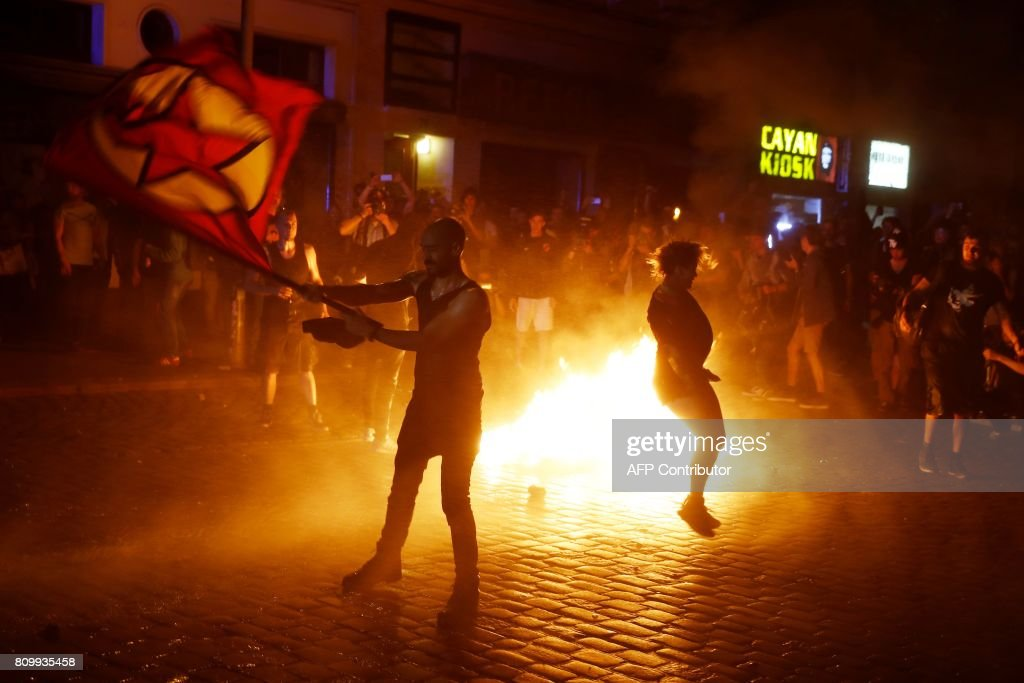 TOPSHOT - Riot police use water cannon to put of burning bins as a protester waves a flag after the 'Welcome to Hell' rally against the G20 summit in Hamburg, northern Germany on July 6, 2017. Leaders of the world's top economies will gather from July 7 to 8, 2017 in Germany for likely the stormiest G20 summit in years, with disagreements ranging from wars to climate change and global trade. / AFP PHOTO / Odd ANDERSEN