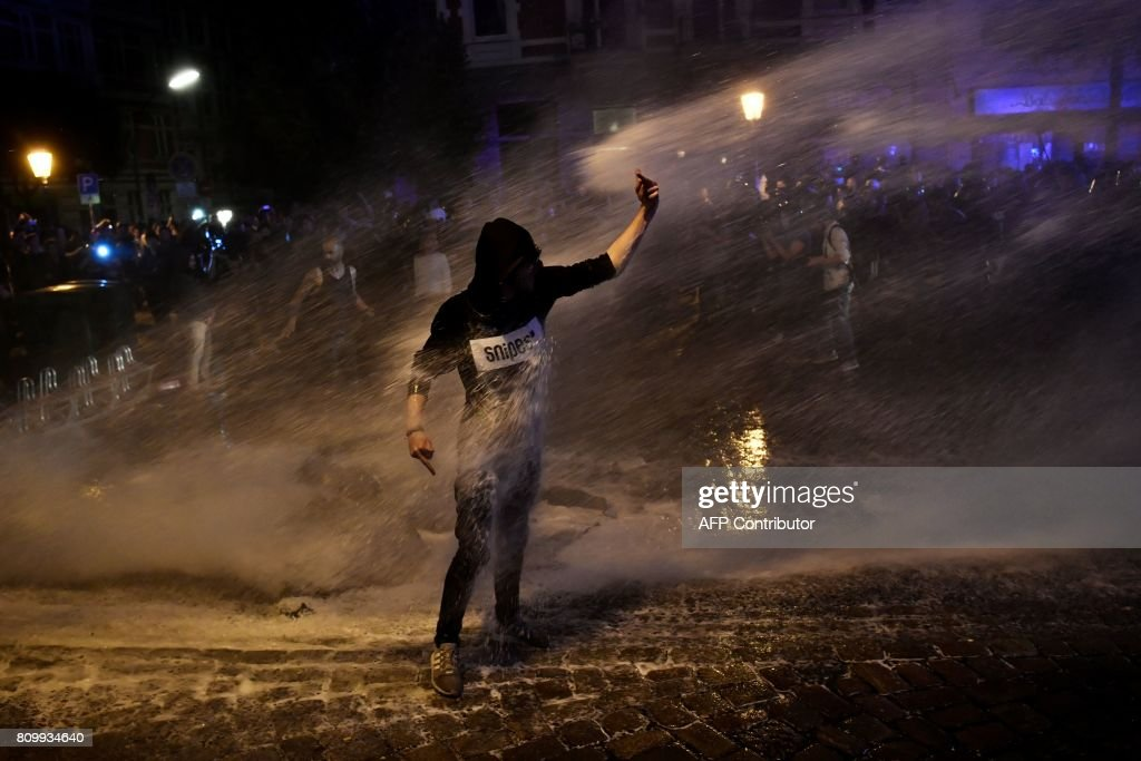 TOPSHOT - Riot police use water cannon to put of burning bins as a protester gestures after the 'Welcome to Hell' rally against the G20 summit in Hamburg, northern Germany on July 6, 2017. Leaders of the world's top economies will gather from July 7 to 8, 2017 in Germany for likely the stormiest G20 summit in years, with disagreements ranging from wars to climate change and global trade. / AFP PHOTO / John MACDOUGALL