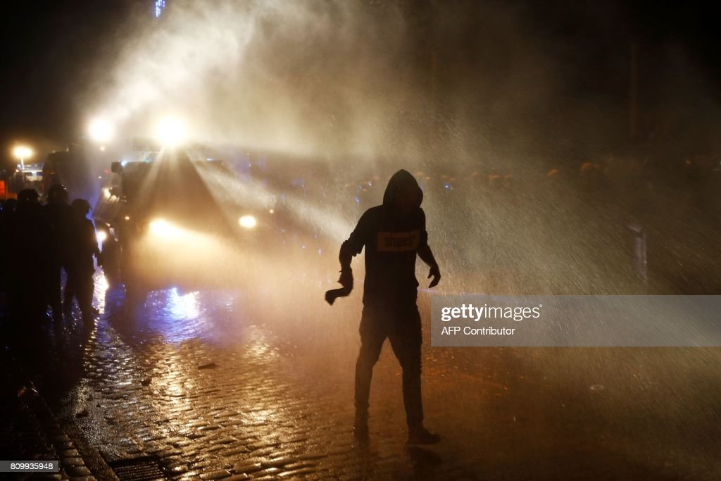 TOPSHOT - Riot police use water cannon to put of burning bins as a protester runs off after the 'Welcome to Hell' rally against the G20 summit in Hamburg, northern Germany on July 6, 2017. Leaders of the world's top economies will gather from July 7 to 8, 2017 in Germany for likely the stormiest G20 summit in years, with disagreements ranging from wars to climate change and global trade. / AFP PHOTO / Odd ANDERSEN