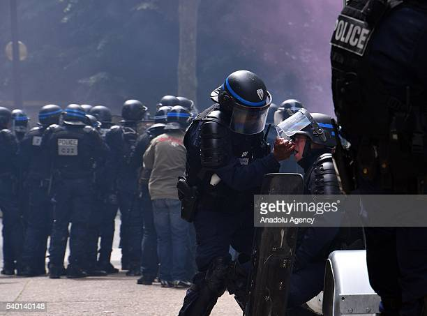 A riot police uses an inhaler after his eyes with saline solution after he receives tear gas during a national demonstration and strike against the...