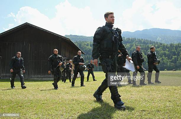 Riot police walk across a field next to a hay barn prior to a demonstration by activists outside the George Marshall European Center for Security...