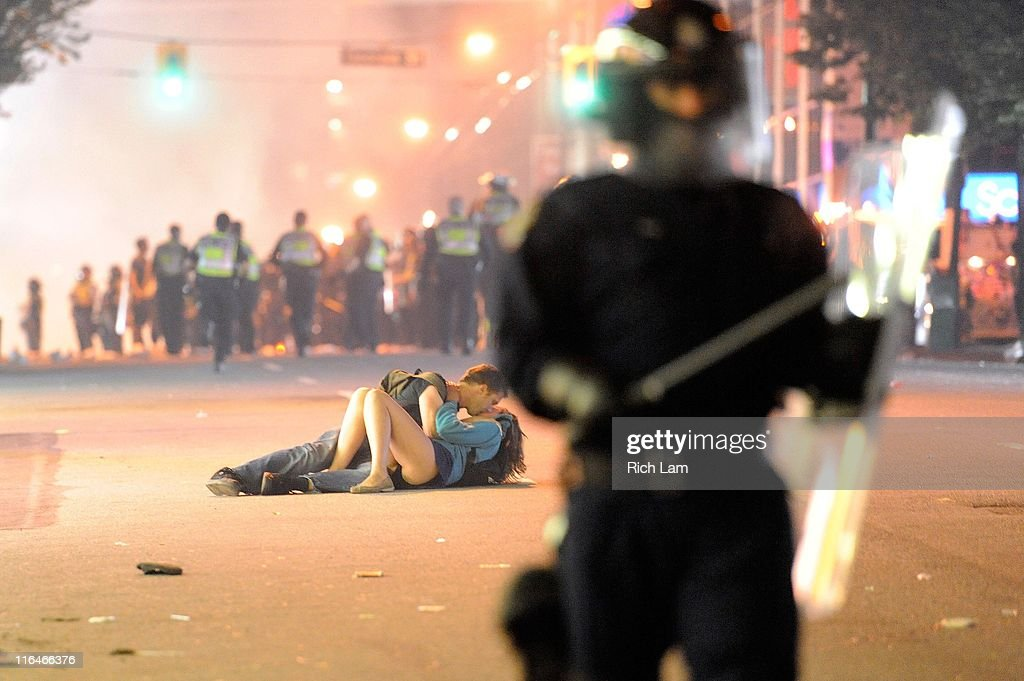 Riot police walk in the street as a couple kiss on June 15, 2011 in Vancouver, Canada. Vancouver broke out in riots after their hockey team the Vancouver Canucks lost in Game Seven of the Stanley Cup Finals.