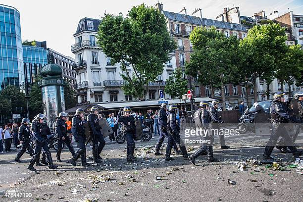 Riot police walk over broken glass bottles and debris littering a road as French cab drivers protest against Uber Technologies Inc's car sharing...