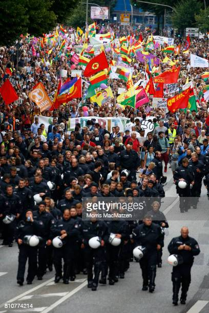 Riot police walks ahead of protesters demonstrate against the G20 economic summit during a protest march on July 08 2017 in Hamburg Germany Hamburg...