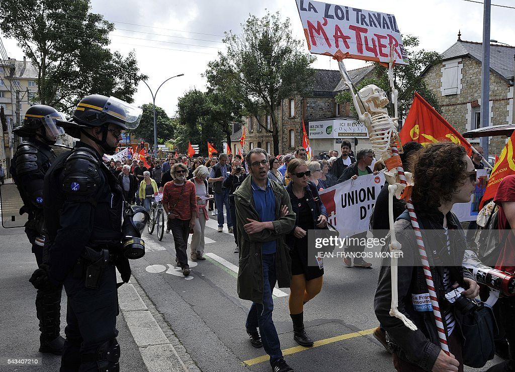 Riot police watch as demonstrators hold a fake skeleton and a sign reading 'The labour law killed me' during a protest against the French controversial labour reforms on June 28, 2016 in Rennes, western France. / AFP / JEAN