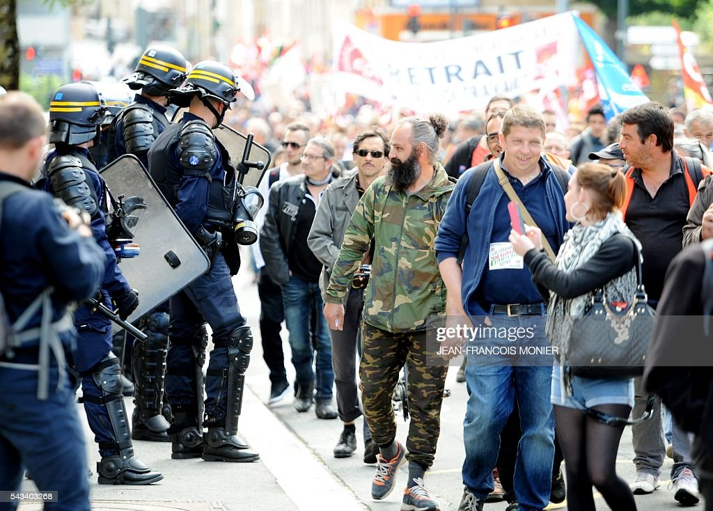 Riot police watch as demonstrators march past during a protest against controversial labour reforms on June 28, 2016 in Rennes. / AFP / JEAN