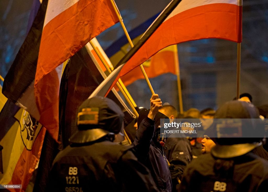 Riot police watch as neo-Nazi brandish flags during a rally to commemorate the 68nd anniversary of the bombing of Dresden on February 13, 2013 in Dresden, eastern Germany, on February 13, 2013. A massive bombing raid by Allied forces on Dresden beginning on February 13, 1945 sparked a firestorm that destroyed much of the historical centre of the city.