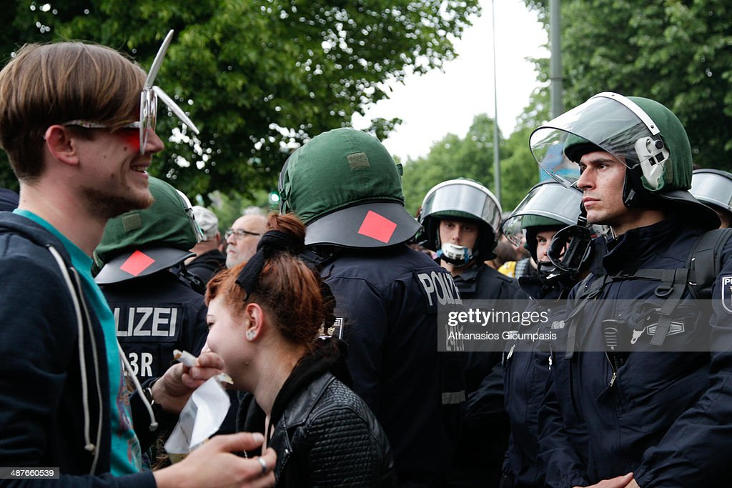 Riot police watch protesters at a May Day celebration on May 1, 2014 in Berlin, Germany. May Day, or International Workers' Day, was established as a public holiday in Germany after 1933 and is observed with gatherings by labour unions and political parties. In some cities, including Hamburg and Berlin, the day in the past has often ended with violent clashes between police and mostly left-wing demonstrators.