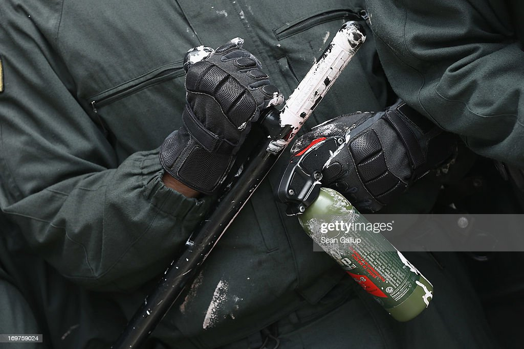 A riot policeman clutches a club and a bottle of pepper spray stained with paint thrown by a protester during the main Blockupy demonstration in the...