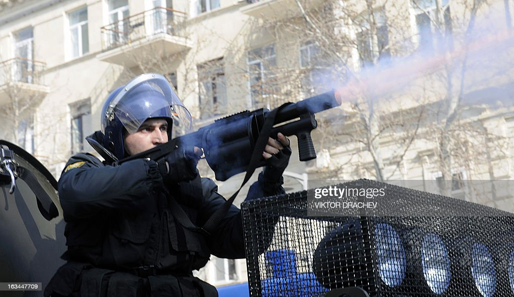A riot policeman fires tear gas to disperse people during a rally against soldiers death in the national Azerbaijan's army in Baku on March 10, 2013. Azeri police on Sunday arrested about 60 protesters demonstrating against the deaths of 15 soldiers who died in accidents or were allegedly abused by their officers in the past two months.