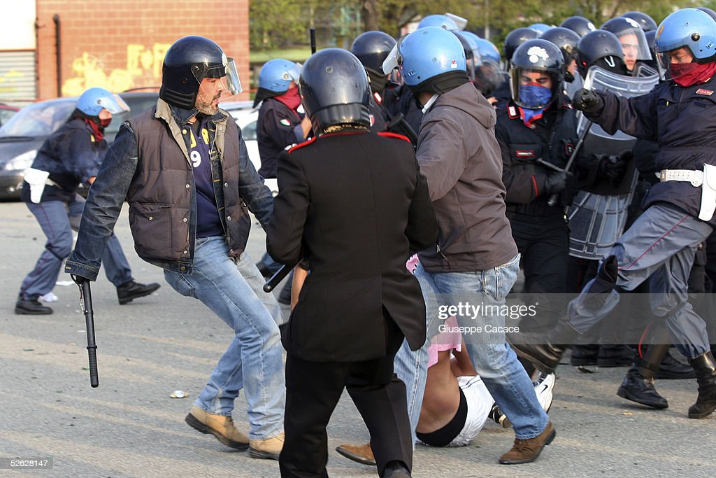Riot Policeman kick a Juventus fans during clashes before the Juventus v Liverpool UEFA Champions League Match April 13 2005 in Turin Italy