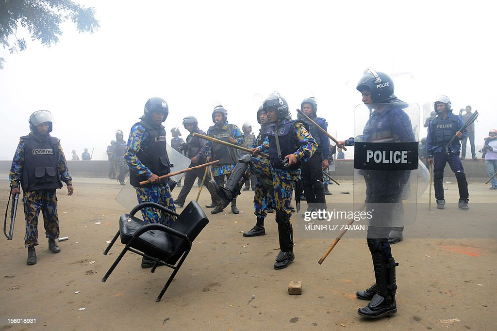 A riot policeman kicks a chair as they remove a roadblock erected by Bangladesh Nationalist Party (BNP) supporters during a protest in Narayanganj, on the outskirts of Dhaka, on December 9, 2012. Bangladesh police fired rubber bullets and tear gas at opposition protesters across the country as they tried to block roads and highways to press for their demand for polls under a caretakler government. AFP PHOTO/Munir uz ZAMAN