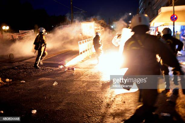 A riot policeman runs past flames from exploded petrol bombs thrown by a small group of antiestablishment demonstrators in front of parliament on...