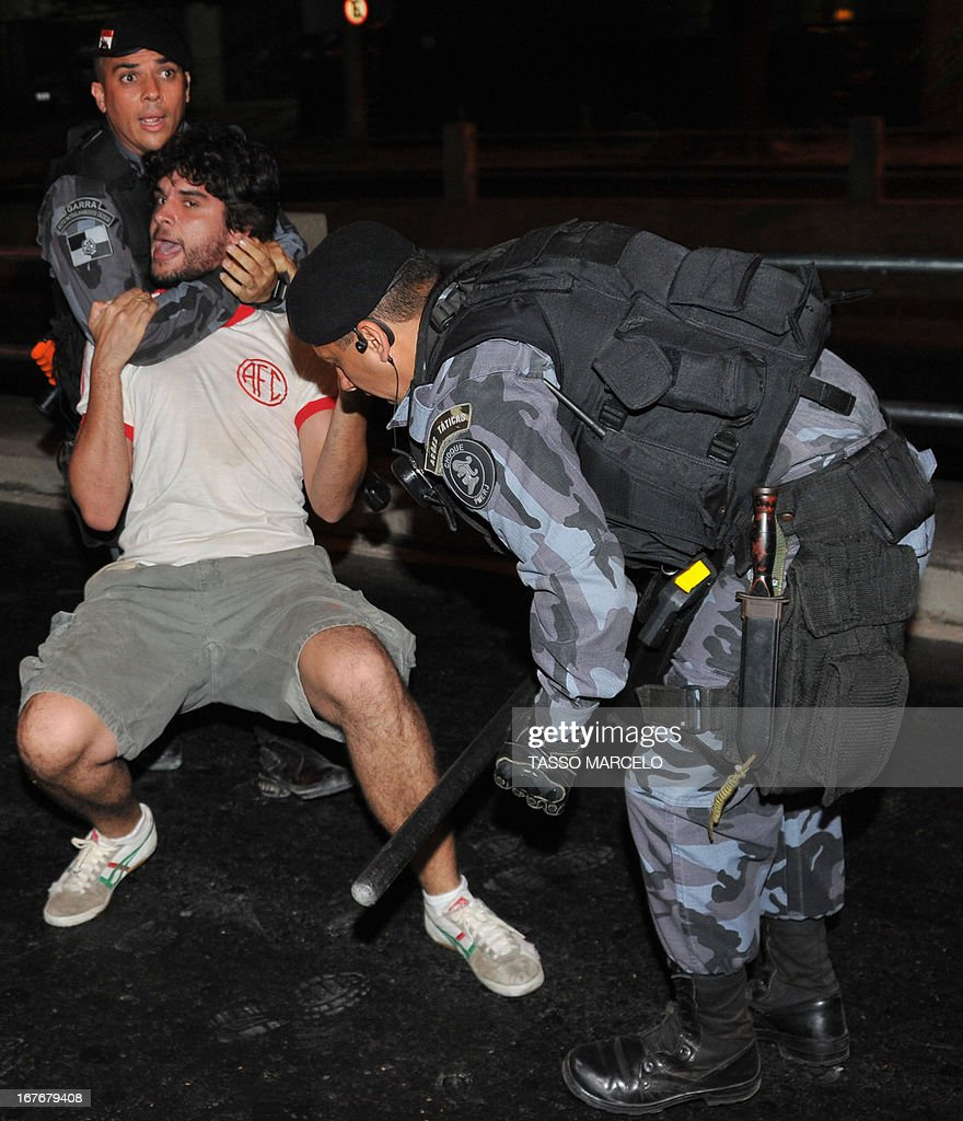Riot policemen arrest a demonstrator outside the Mario Filho --Maracana-- stadium during a protest against its privatization and the demolition of the former Indigenous Museum, at the time that a test event is taking place in the Maracana stadium, in Rio de Janeiro on April 27, 2013. The Maracana will host the upcomig Confederations Cup --next June--, the Brazil 2014 FIFA World Cup and the 2016 Summer Olympics. AFP PHOTO / TASSO MARCELO