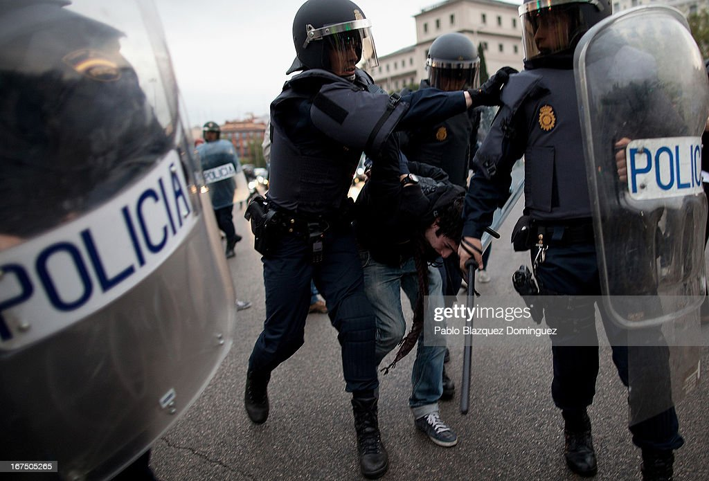 Riot policemen arrest a protester near Atocha Station on April 25, 2013 in Madrid, Spain. Demonstrators marched from three locations in central Madrid in an attempt to converge on parliament, demanding a constitutional reform and protesting against financial measures introduced by Spanish Prime Minister Mariano Rajoy.