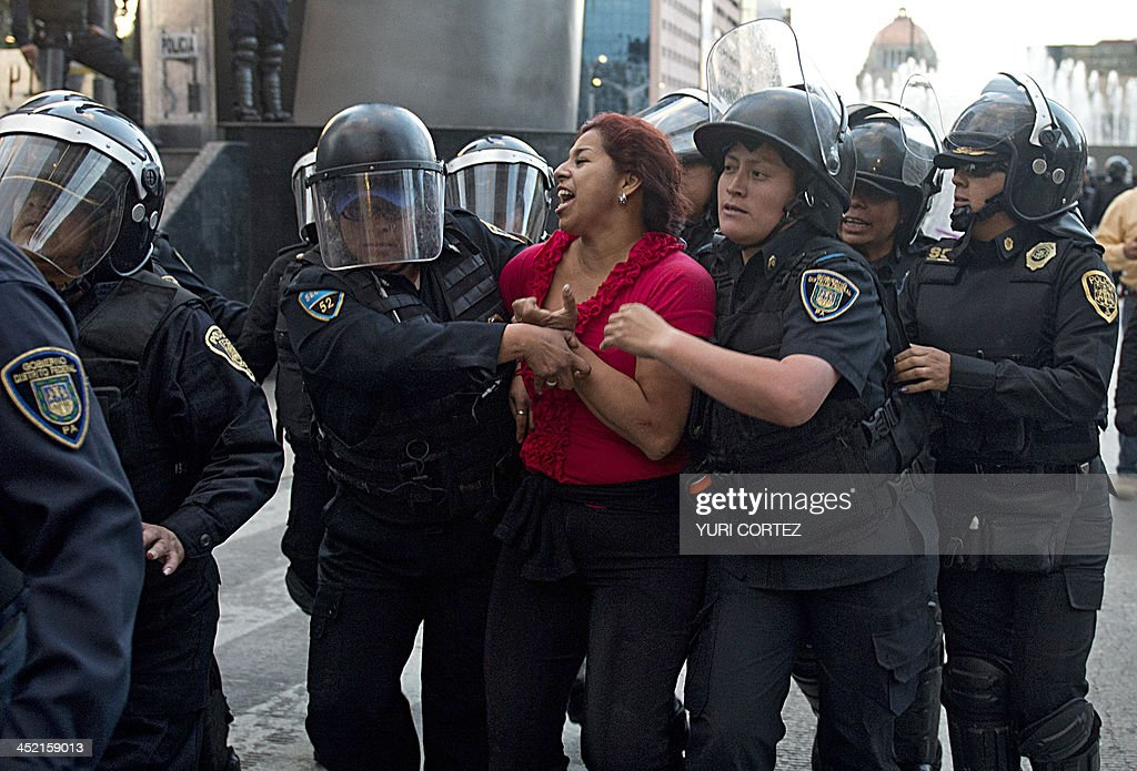 Riot policemen arrest a teacher during a protest against the education reform in Mexico City on November 26 2013 President Enrique Pena Nieto pushed...