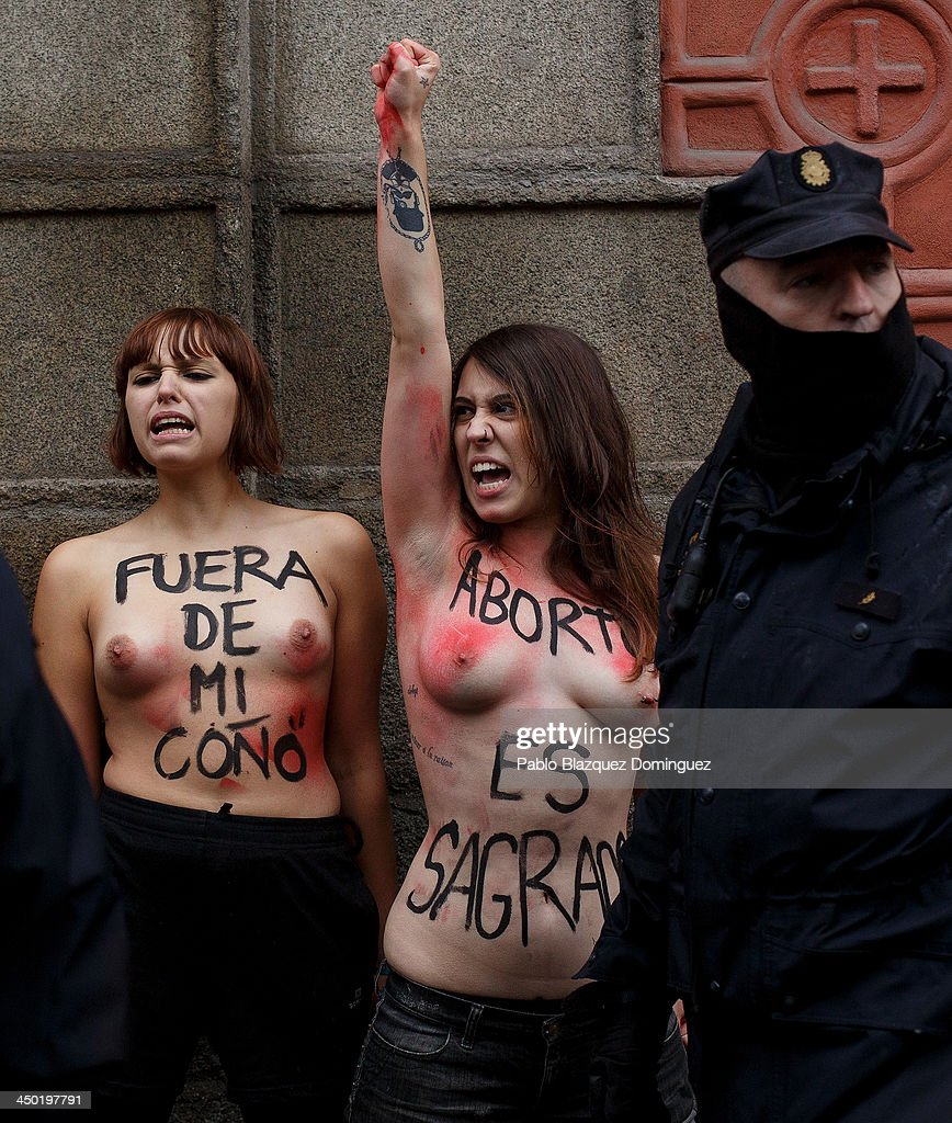 Riot policemen arrest FEMEN group activist with body paintings reading (L) 'get out of my vagina' and (R) 'abortion is sacred' as a Pro-Life demonstration takes place on Alcala Street on November 17, 2013 in Madrid, Spain. The Pro-Life rally was demonstrating against women's right to abort.