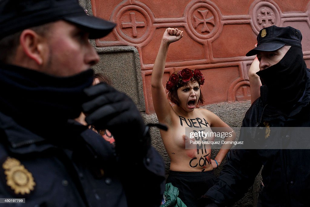 Riot policemen arrest FEMEN group activists with body painting reading 'get out of my vagina' as a Pro-Life demonstration takes place on Alcala Street on November 17, 2013 in Madrid, Spain. The Pro-Life rally was demonstrating against women's right to abort.