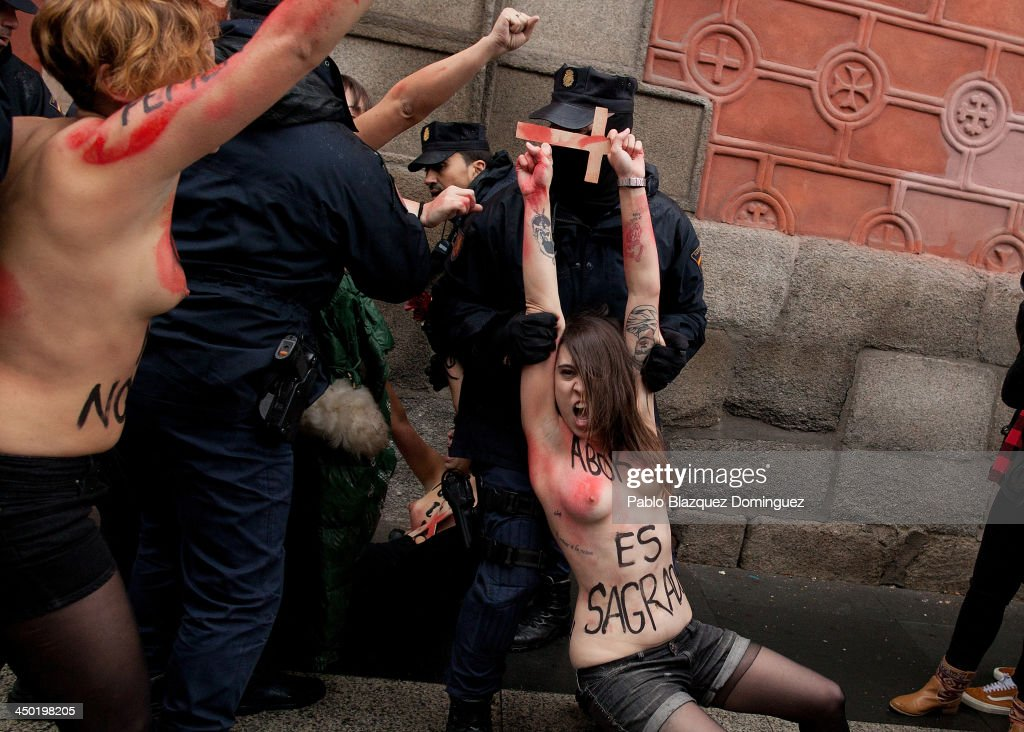 Riot policemen arrest FEMEN group activists with body painting (R) reading 'abortion is sacred' as a Pro-Life demonstration is arriving at Alcala Street on November 17, 2013 in Madrid, Spain. The Pro-Life rally was demonstrating against women's right to abort.