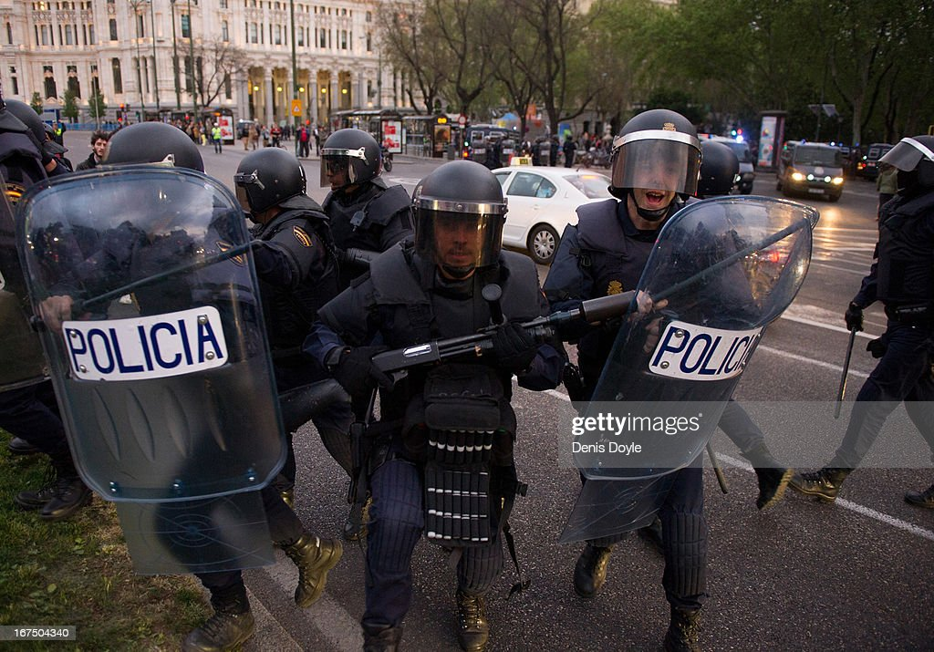 Riot policemen charge at demonstrators during disturbances at a demonstration on April 25, 2013 in Madrid, Spain. Demonstrators marched from three locations in central Madrid in an attempt to converge on parliament, demanding a constitutional reform and protesting against financial measures introduced by Spanish Prime Minister Mariano Rajoy.