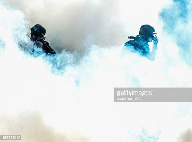 TOPSHOT Riot policemen clash with opposition demonstrators in Caracas on May 24 2017 Venezuela's President Nicolas Maduro formally launched moves to...
