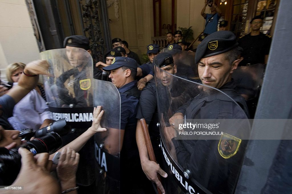 Riot policemen evacuate the Supreme Court of Justice headquarters during the swearing ceremony of the new judges in Montevideo on February 15, 2013. Members of Human Rights organizations occupied the building in support of jugde Mariana Mota, who was transfered from her penal office, where she worked on about 50 cases of human rights abuses during the 1973-1985 dictatorship in Uruguay to a civilian court . AFP PHOTO/Pablo PORCIUNCULA