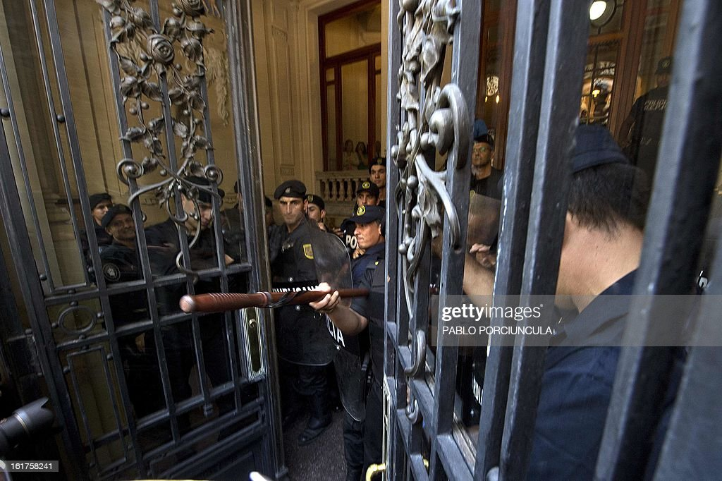 Riot policemen evacuate the Supreme Court of Justice headquarters during the swearing ceremony of the new judges in Montevideo on February 15, 2013. Members of Human Rights organizations occupied the building in support of jugde Mariana Mota, who was transfered from her penal office to a civilian court where she worked on about 50 cases of human rights abuses during the 1973-1985 dictatorship in Uruguay. AFP PHOTO/Pablo PORCIUNCULA