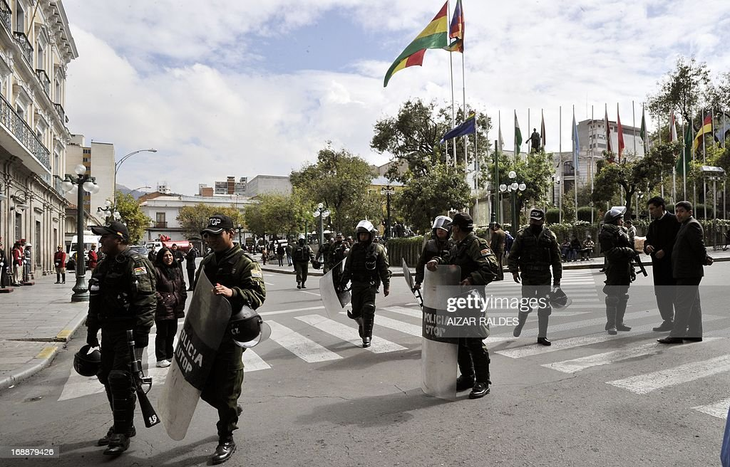 Riot policemen guard the surrouindings of the Plaza de Armas square as workers on the eleventh day of an indefinite strike called by the Bolivian Workers' Central union (COB) to demand the government for a pension equivalent to 100% of their salaries, demonstrate in La Paz on May 16, 2013. AFP PHOTO/Aizar Raldes