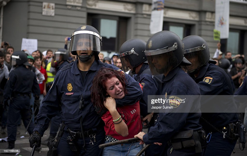Riot policemen hold back a demonstrator during clashes around the Spanish parliament in a protest against spending cuts and the government of Mariano Rajoy on September 25, 2012 in Madrid, Spain. Demonstrators from various organizations, demanding a new constitutional process, are marching today from three different locations in the center of Madrid to the lower house in the Spanish parliament.