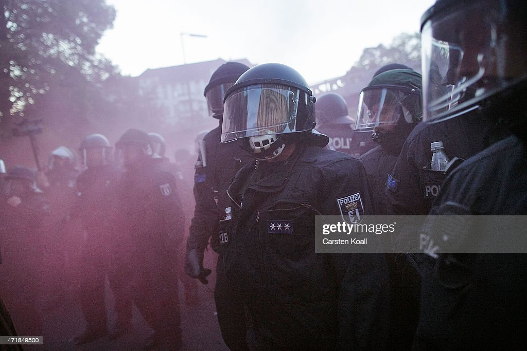 Riot policemen in red smoke during a 'Revolutionary May 1st' May Day march on May 1 2015 in Berlin Germany Anticapitalist demonstrations on May Day...