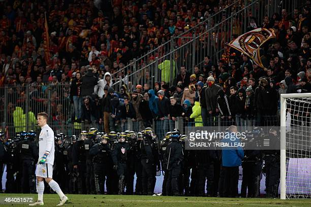 Riot policemen stan guard by the tribune of Lens fans during a game interruption after Lens fans used flares during the French L1 football match...