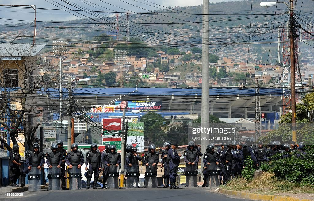 Riot policemen stand guard at the entrance of the national stadium to prevent members of the National Front of Popular Resistance from entering to...