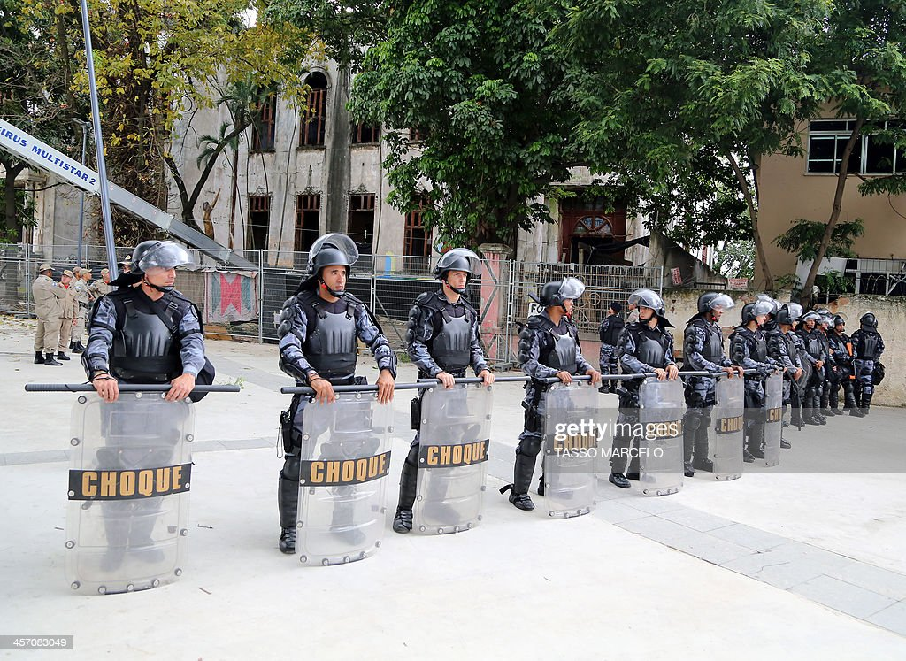 Riot policemen stand guard during a demonstration near the Museu do Indio (Indian Museum) 'Aldea Maracana' (Maracana Village) in Rio de Janeiro, Brazil, on December 16, 2013. The demonstrators, among whom there were some 30 Amazonic natives, seized the museum protesting against its scheduled demolition to continue the works in the Mario Filho 'Maracana' stadium ahead of the Brazil 2014 FIFA World Cup.