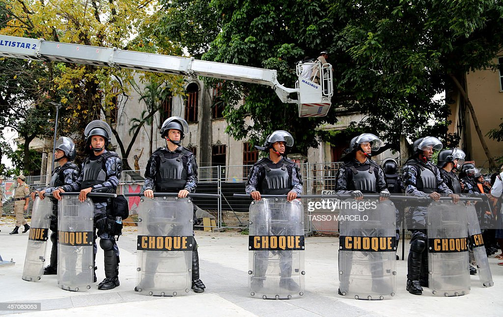 Riot policemen stand guard in front of the Museu do Indio (Indian Museum) 'Aldea Maracana' (Maracana Village) during a demonstration in Rio de Janeiro, Brazil, on December 16, 2013. The demonstrators, among whom there were some 30 Amazonic natives, seized the museum protesting against its scheduled demolition to continue the works in the Mario Filho 'Maracana' stadium ahead of the Brazil 2014 FIFA World Cup. AFP PHOTO/TASSO MARCELO