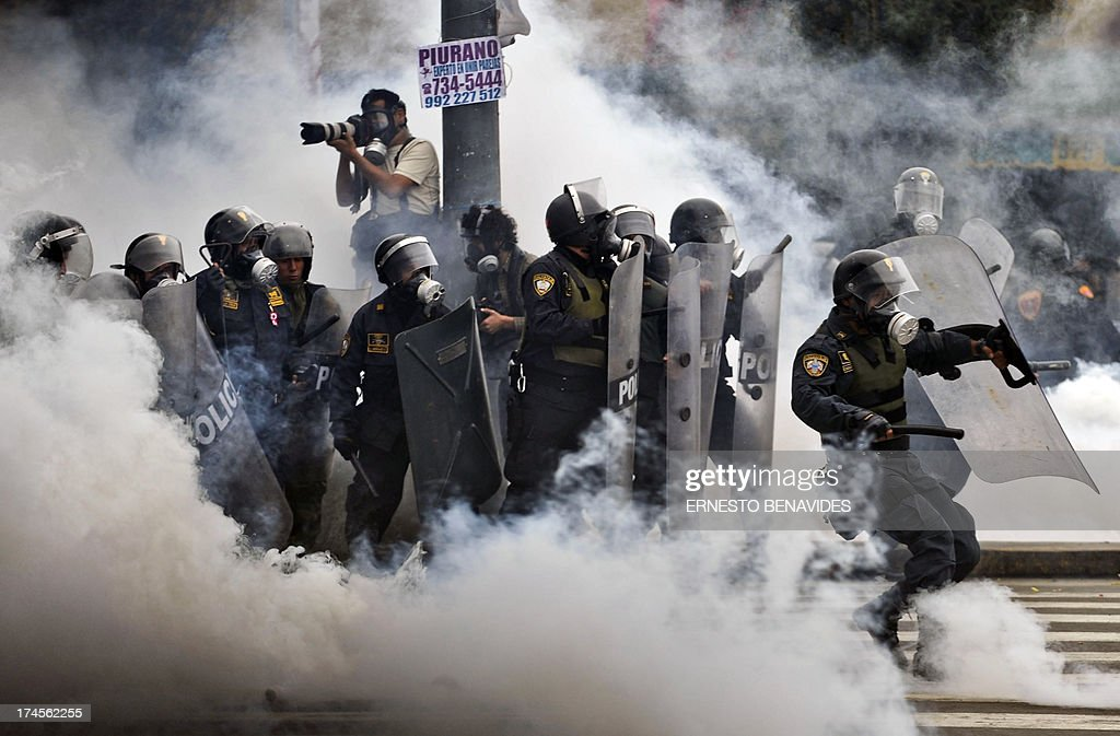 Riot policemen stand in a tear gas cloud during clashes within a student and workers protest against the government, in Lima on July 27, 2013. Students protested against a bill --that if passed-- would reduce university autonomy, whilst workers did it against a new civil service law which could bring massive dismissals, according to the workers' union. AFP PHOTO / ERNESTO BENAVIDES