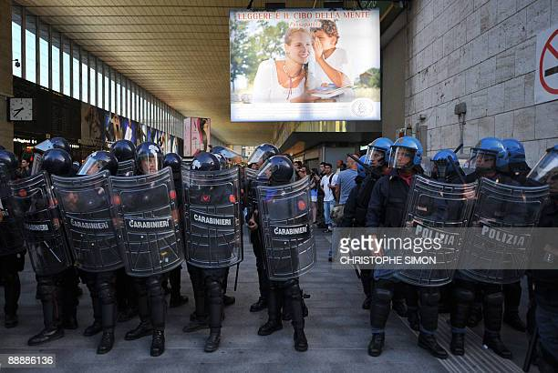 Riot policemen stand under a placard reading 'reading is feeding your head' during clashes with protesters at Termini station at the end of a...
